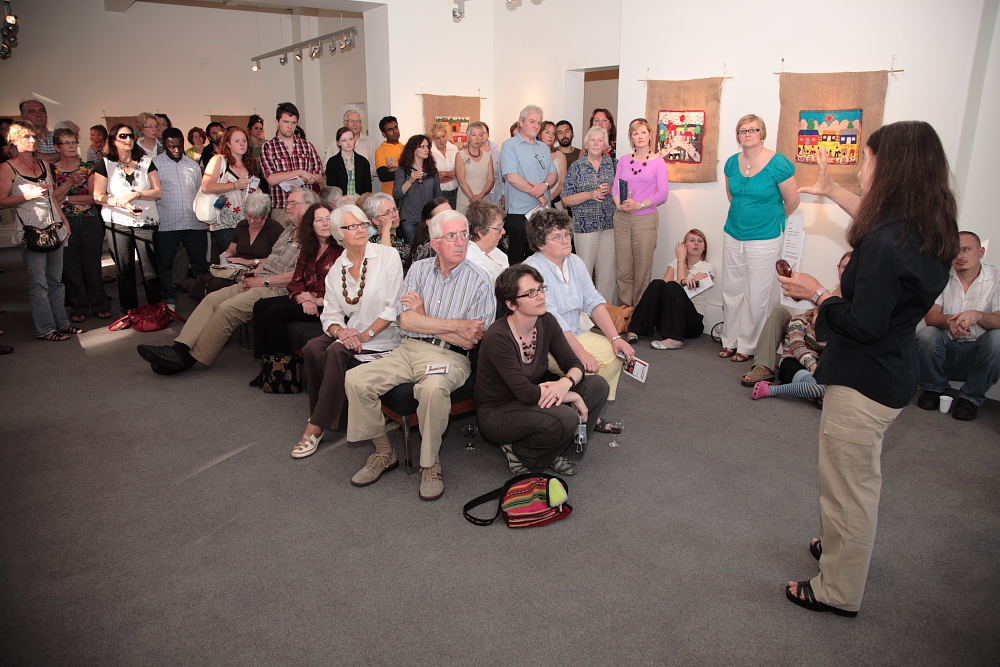 Attendees listening intently to curator Roberta Bacic at the exhibition opening event. (Photo: Martin Melaugh)