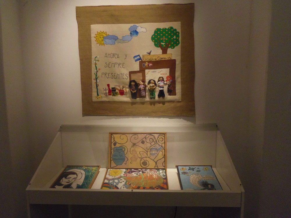 "The arpillera ""Irene, Marta, Hilda, Patricia: Ahora y Siempre Presentes / Irene, Marta, Hilda, Patricia: Now and Always Present"" on display with commemoration tiles from Escuela de Cerámica. (Photo: Ana Zlatkes)"